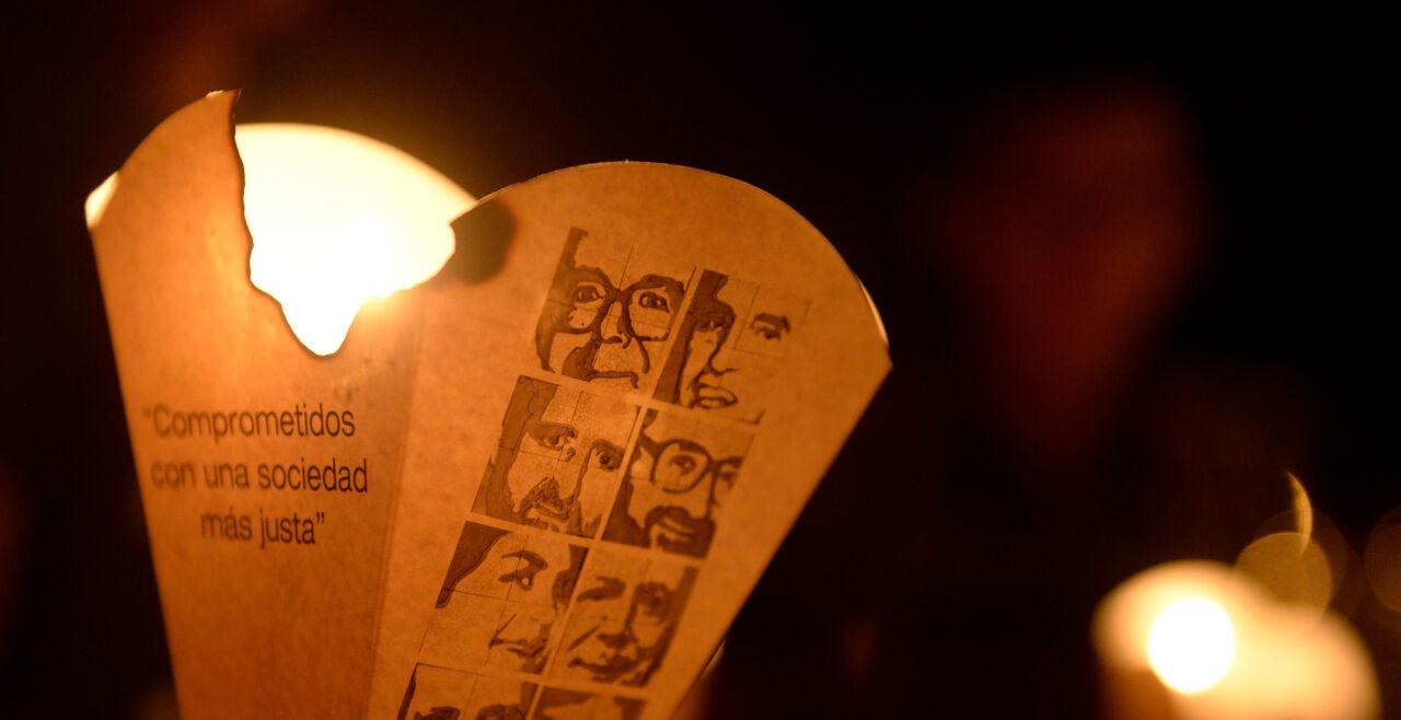 Märtyrer-Andenken - © Foto: APA / Marvin Recinos (Kerze bei Gedenkprozession, auf dem Windfang die Fotos der Ermordeten)