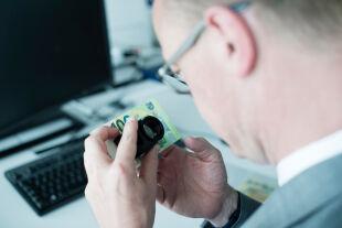 """Detailarbeit - Harald Deinhammer kontrolliert die Sicherheitsmerkmale einer 100-Euro-Note nach der Devise """"Fühlen, Sehen, Kippen"""".<br />"""